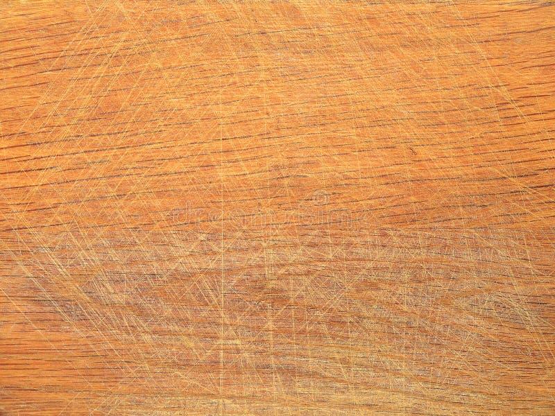 有很多刀片标记的老棕色木厨房切板在切食物以后,抽象背景纹理 免版税库存照片