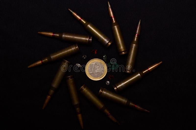 有很多宝石的步枪弹药在黑背景的一枚欧洲硬币附近 象征金钱和一个的战争世界` s p 库存照片