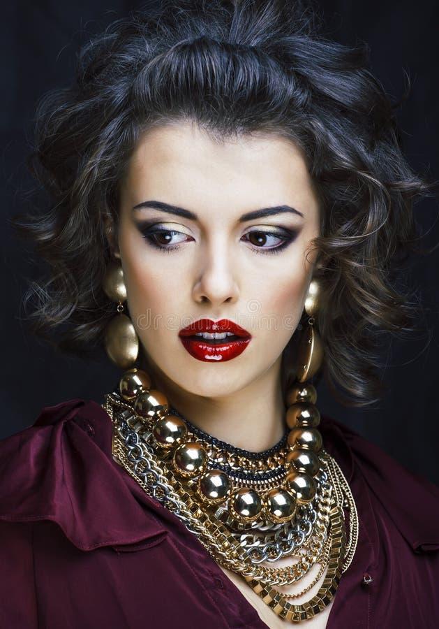 有很多金首饰的秀丽富有的深色的妇女, hispani 免版税库存图片