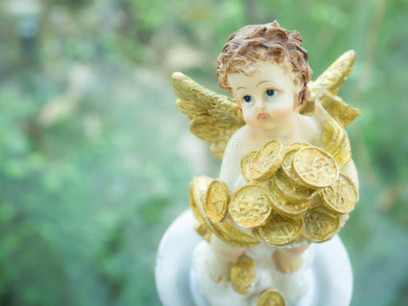 有很多金黄金钱意思的丘比特小雕象时运和金钱在婚姻以后 库存照片