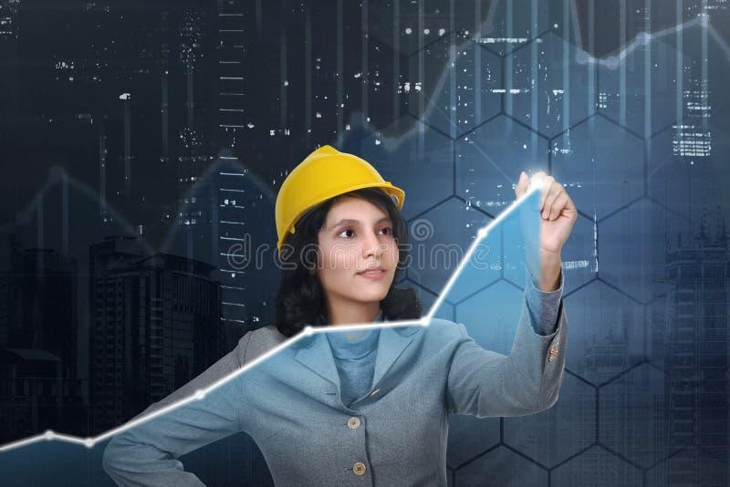 有得出真正图的黄色帽子的亚裔建筑师妇女 免版税图库摄影