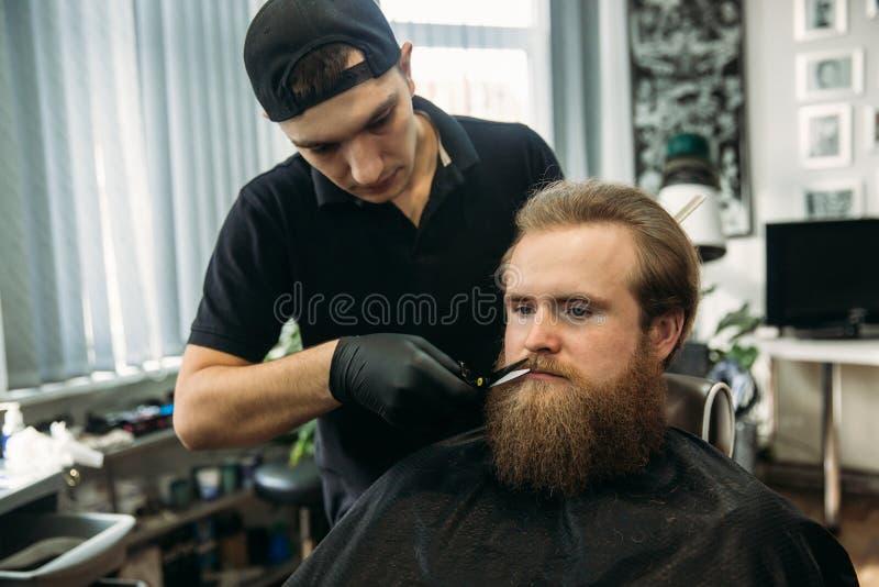 有得到时髦的头发刮,理发的长的胡子的有胡子的人,与剃刀由理发师在理发店 免版税库存图片