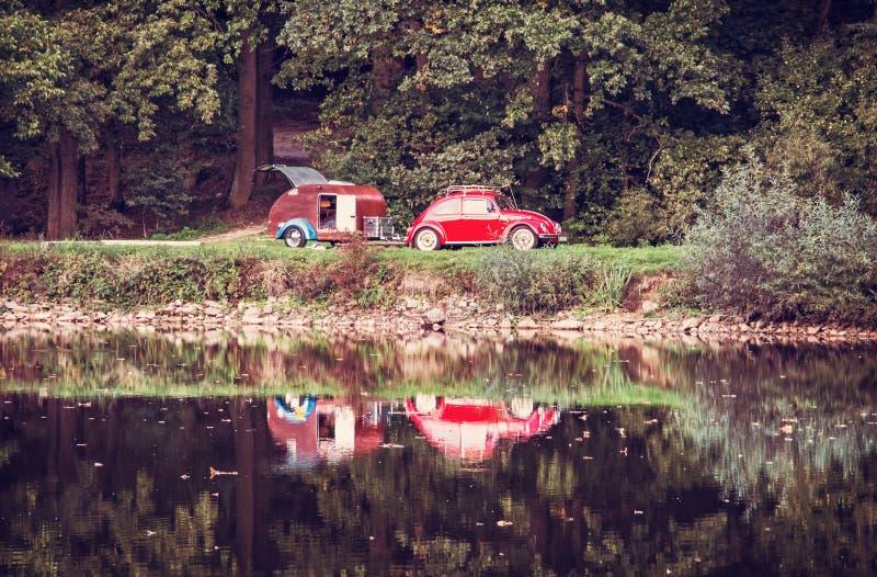 有微型有蓬卡车的历史的汽车在湖,红色过滤器被反射 免版税库存图片
