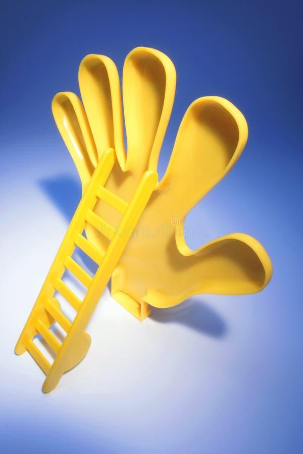 有微型梯子的塑料手 免版税库存图片