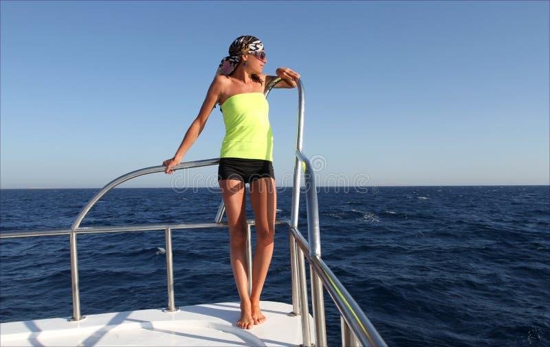 有微小的图的美女在一条游艇在海,海风景,年轻逗人喜爱的女性模型以晒黑,大海视图 免版税图库摄影