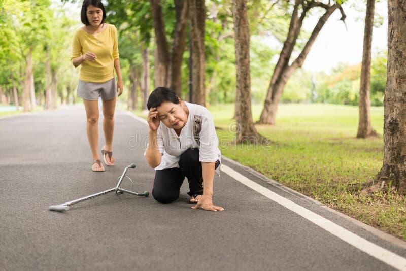 有微弱的开会的资深亚裔妇女在地板上在跌倒以后,女性小心和支持 免版税库存图片