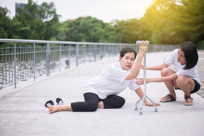 有微弱的开会的资深亚裔妇女在地板上在跌倒以后,女性小心和支持 免版税库存照片