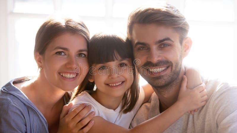 有微笑小逗人喜爱的女儿的幸福家庭看照相机 图库摄影