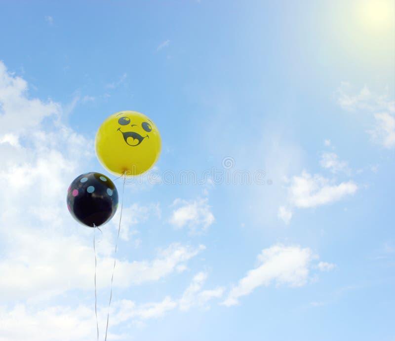有微笑的大黄色气球在他的面孔 库存图片