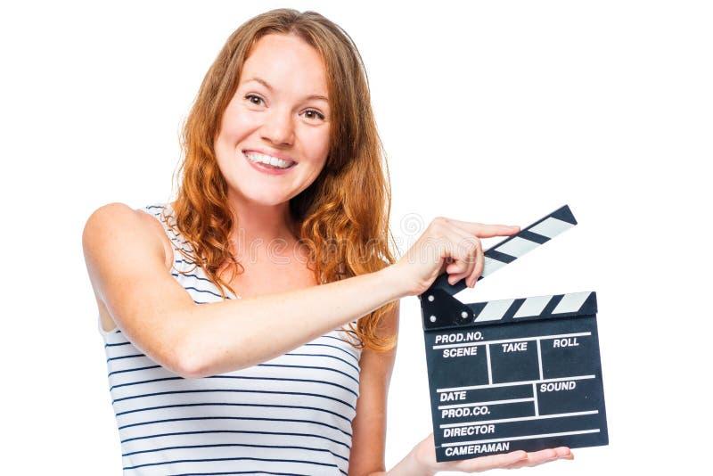 有微笑的女孩拿着在白色的一个电影拍板 库存图片