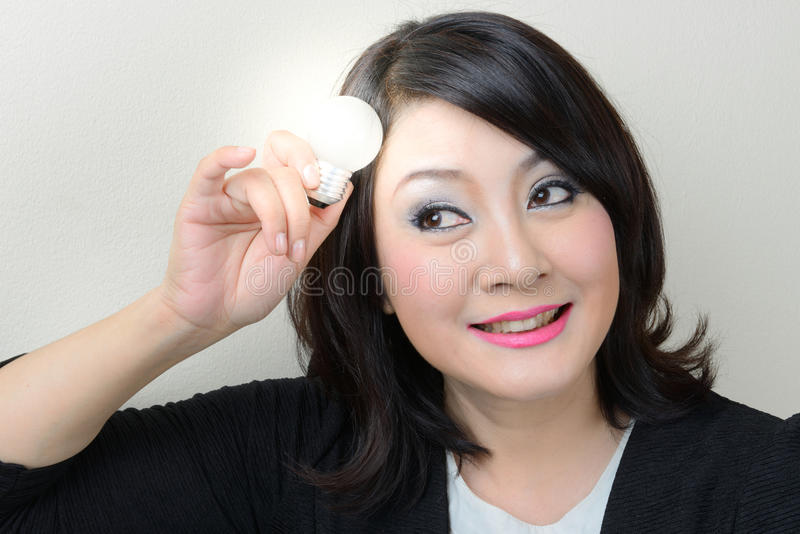 有微笑的女实业家与明亮的电灯泡的一个想法 免版税库存图片