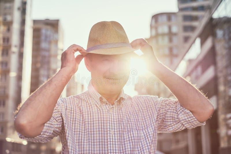 有微笑的帽子的退休的资深西班牙人站立和 免版税库存图片