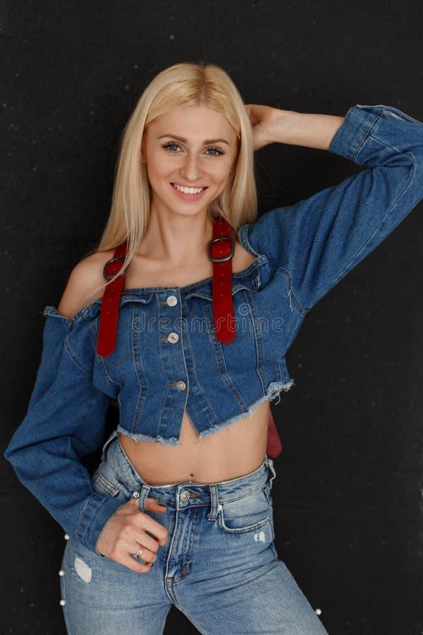 有微笑的快乐的美丽的年轻可爱的愉快的妇女在有蓝色牛仔裤的时兴的牛仔布衣裳在黑墙壁附近 图库摄影