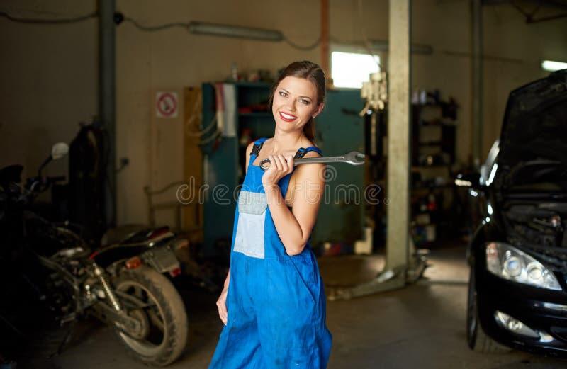 有微笑的技工妇女在修理车库的工作服 免版税图库摄影