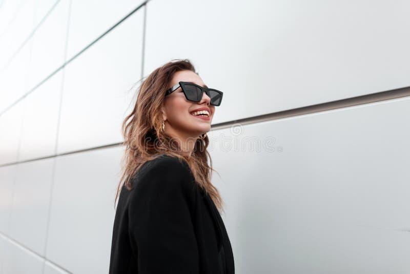 有微笑的正面快乐的年轻行家妇女在一时兴的黑色大衣的太阳镜在现代灰色墙壁附近站立 库存图片