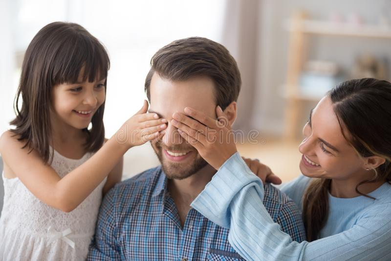有微笑的爸爸的孩子关闭的眼睛的妻子做惊奇 免版税图库摄影