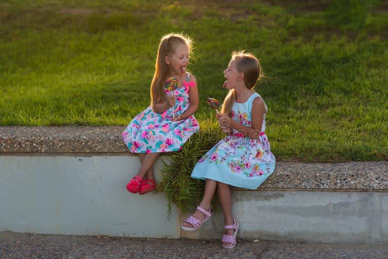 有微笑的眼睛的两美丽的女孩与色的棒棒糖 孩子愉快的画象  免版税库存照片