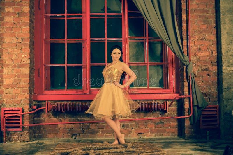 有微笑的逗人喜爱的女孩在毛皮地毯的一件金礼服站立在一个大红色窗口附近在晚上 库存图片