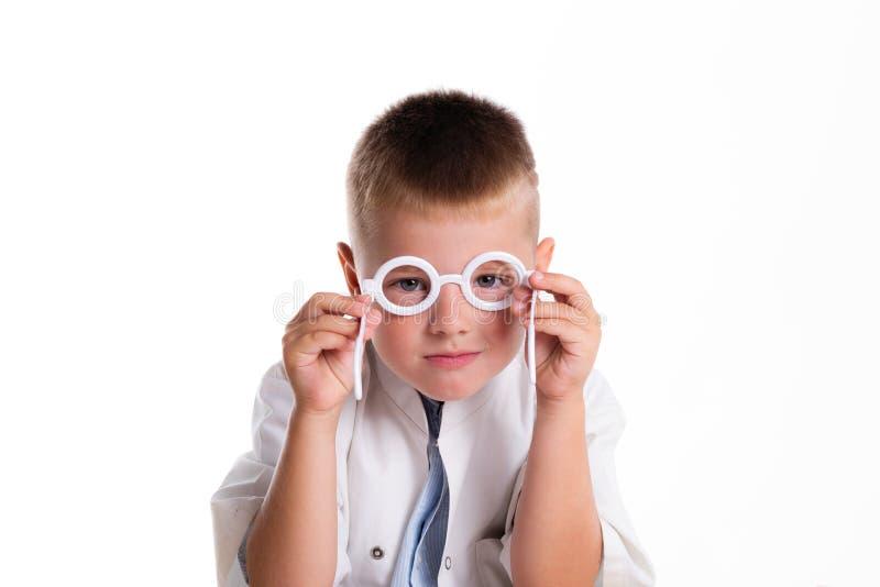 有微笑的逗人喜爱的矮小的医生男孩在坐在他的书桌的面孔  免版税图库摄影