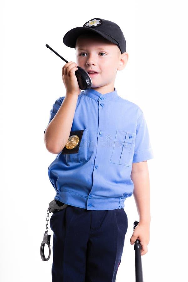 有微笑的逗人喜爱的矮小的警察男孩在面孔和警棒在白色bac 库存图片
