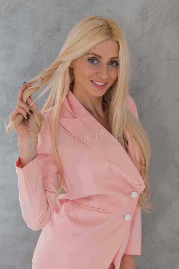 有微笑的逗人喜爱的美丽的迷人的白肤金发的妇女在灰色背景的一套时兴的桃红色衣服 免版税库存图片
