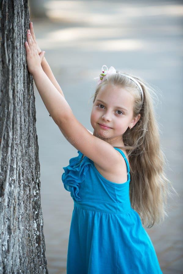 有微笑的面孔的小女婴在室外蓝色的礼服 免版税图库摄影