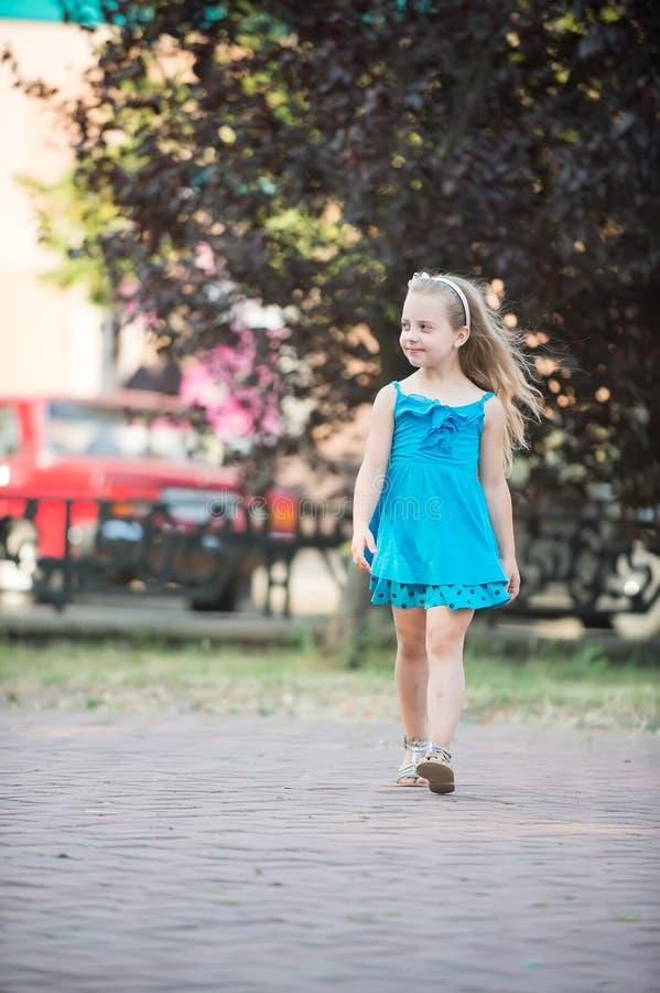 有微笑的面孔的小女婴在室外蓝色的礼服 免版税库存图片