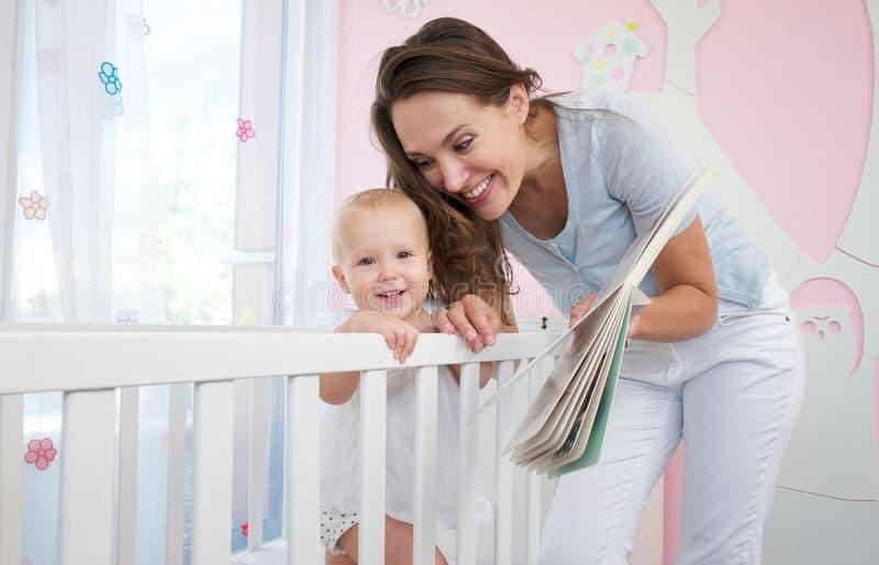 有微笑的婴孩的愉快的母亲一起在卧室 库存照片