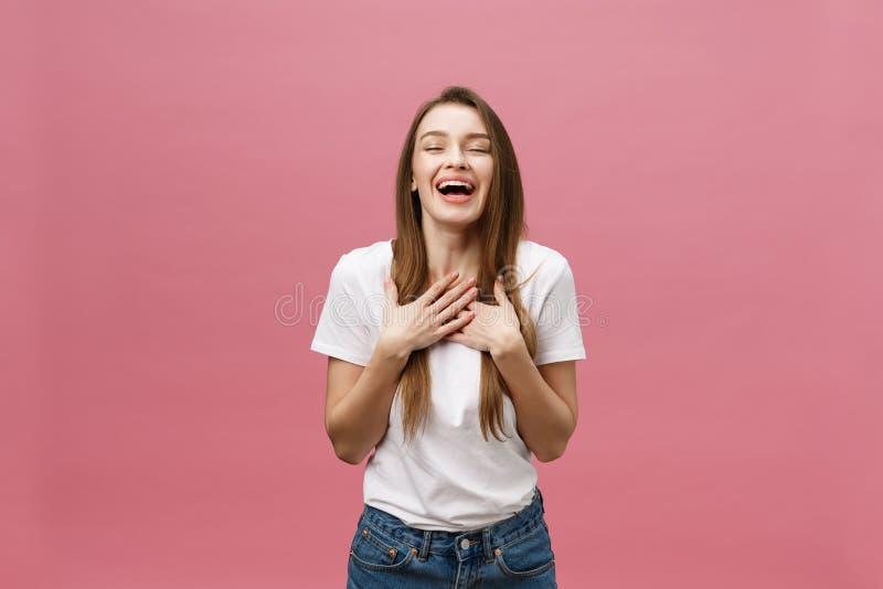 有微笑,呼喊和庆祝的成功愉快的成功的年轻女人在桃红色背景 库存照片