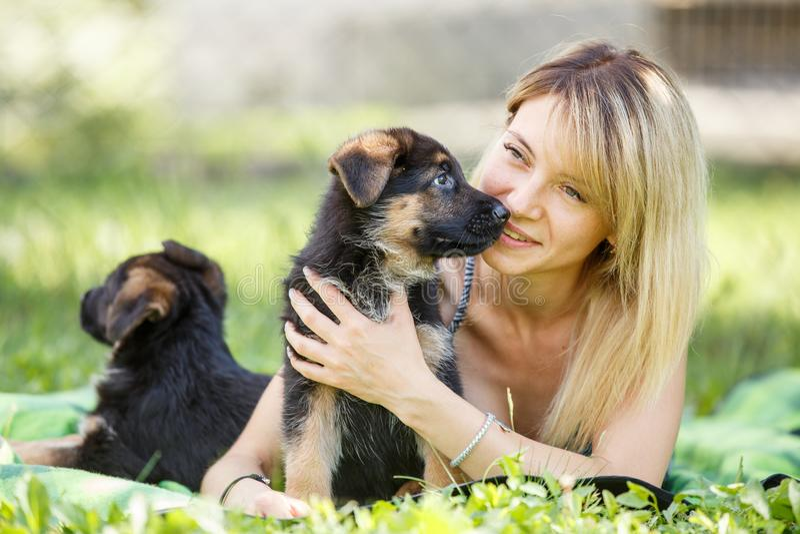 有德国牧羊犬小狗的年轻微笑的妇女  免版税库存图片