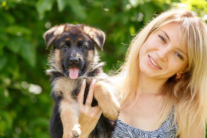 有德国牧羊犬小狗的年轻微笑的妇女  库存图片