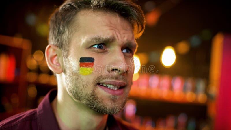 有德国的旗子的人他的面颊的生气与比赛结果,特写镜头 库存图片