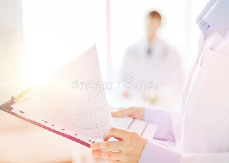 有心电图的女性举行的剪贴板 库存图片