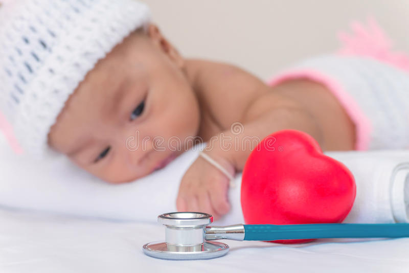 有心脏和女婴的医疗仪器听诊器 免版税库存照片
