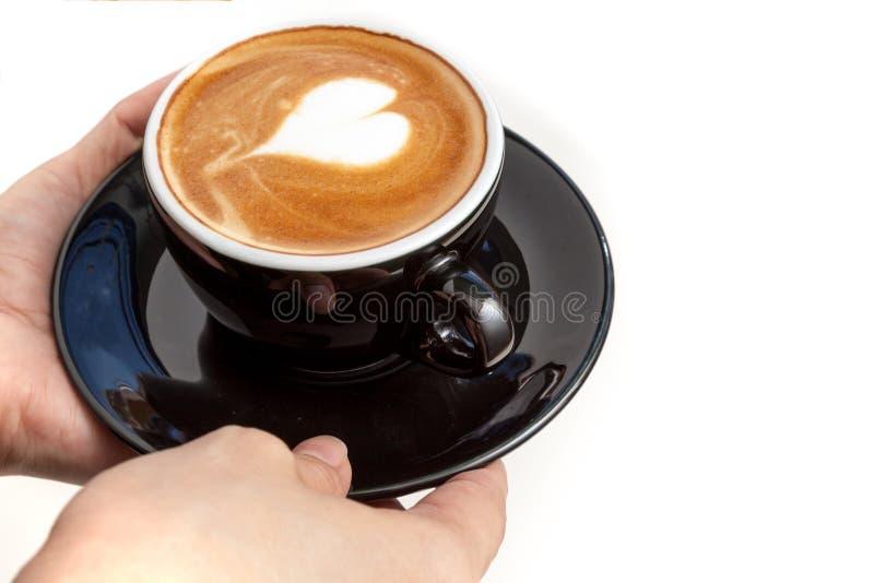 有心脏形状拿铁艺术的咖啡杯在上面,手服务 免版税库存照片