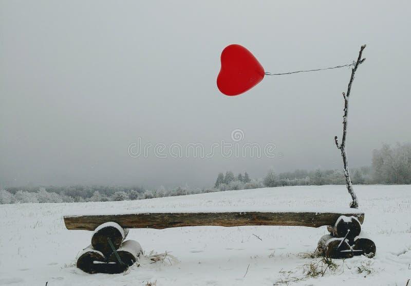 有心脏形状的红色气球在冬天背景 库存图片