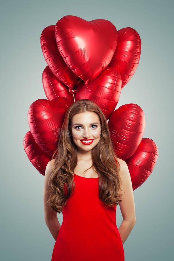 有心脏气球的女孩 有佩带在红色礼服的红色嘴唇构成的妇女 华伦泰人们和情人节概念 免版税图库摄影