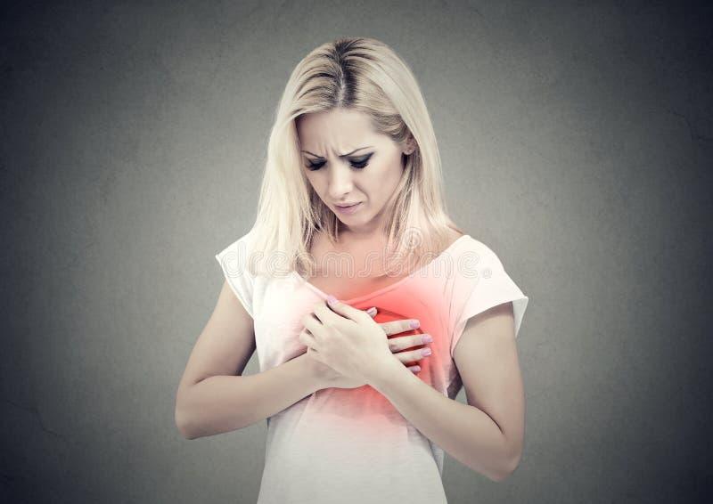 有心脏病发作的,接触她的胸口的痛苦病的妇女上色在红色用手 库存照片