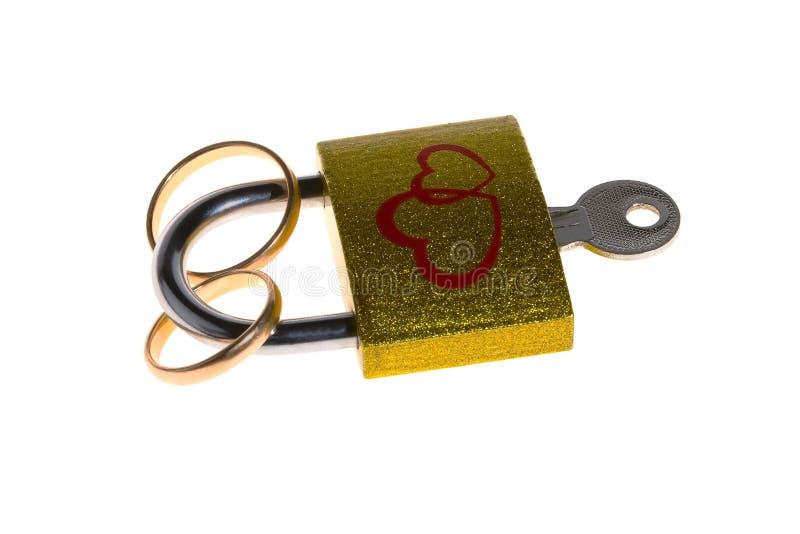 有心脏的图象的一把锁一定的结婚戒指在白色背景的 免版税库存图片