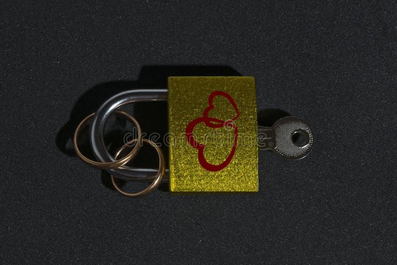 有心脏的图象的一把锁一定的结婚戒指在黑背景的 库存图片