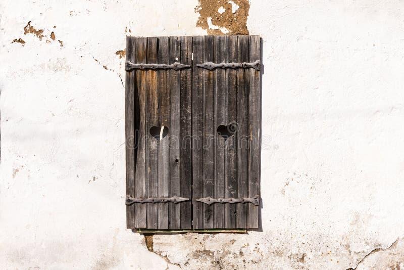有心脏的木灰色快门在老墙壁上 在石墙上的老木窗架 库存照片