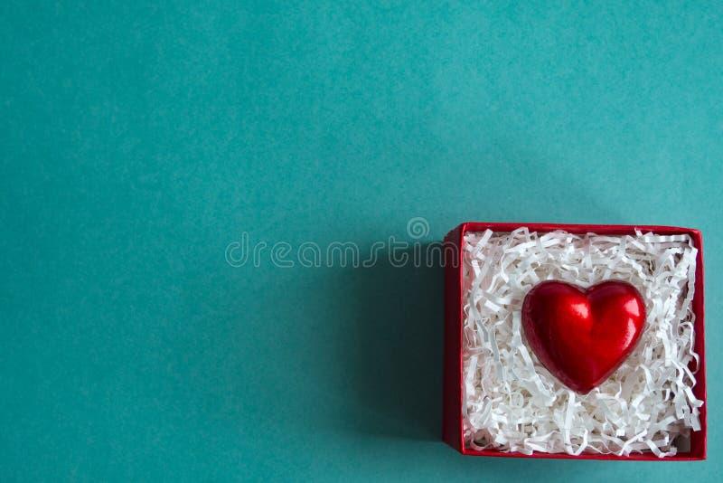 有心脏的红色礼物盒在蓝色背景 复制文本的空间 免版税库存图片