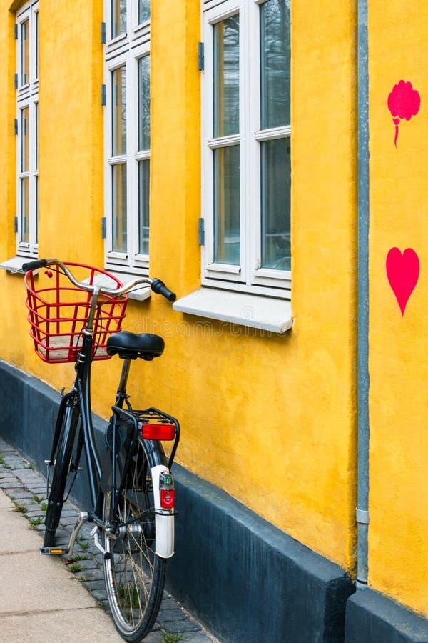 有心脏的自行车在黄色房子墙壁上在哥本哈根 免版税库存图片
