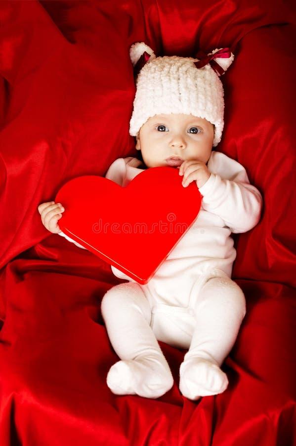 有心脏的逗人喜爱的矮小的婴孩 免版税库存图片