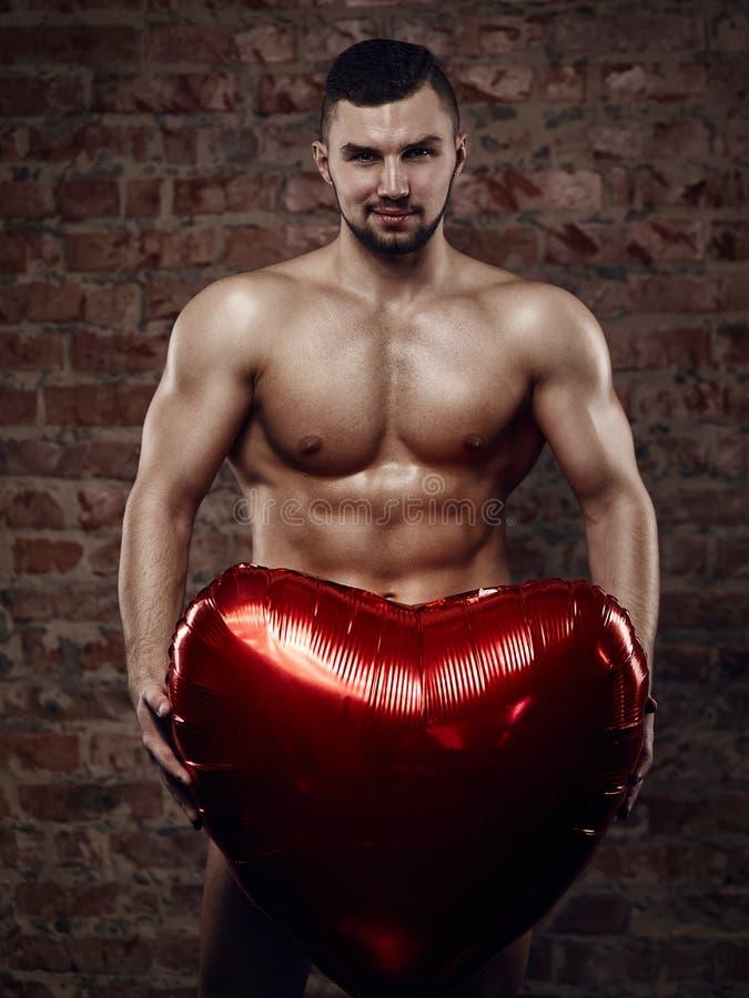有心脏的年轻肌肉人 免版税图库摄影