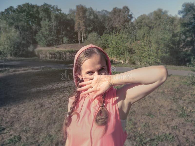 有快乐,嬉戏,恶作剧眼睛的一个女孩用她的手盖她的面孔 桃红色衣裳的一逗人喜爱的年轻女人在公园, 库存照片