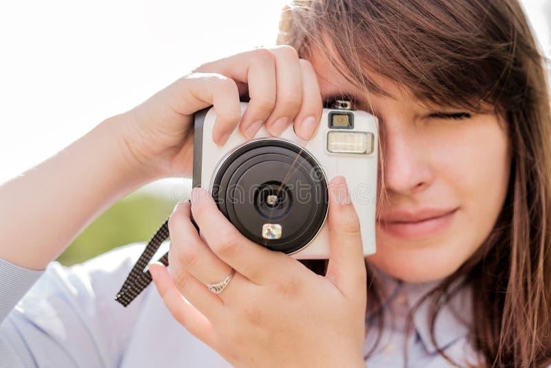 有快速照相机的可爱的年轻长发女孩 库存图片