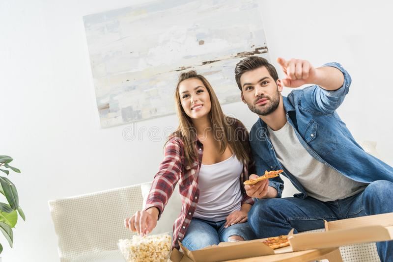 有快餐的夫妇看着电视 库存照片