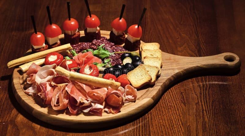 有快餐的委员会在木桌上 在圆的委员会服务的快餐开胃 餐馆盘概念 冷的开胃菜 库存照片