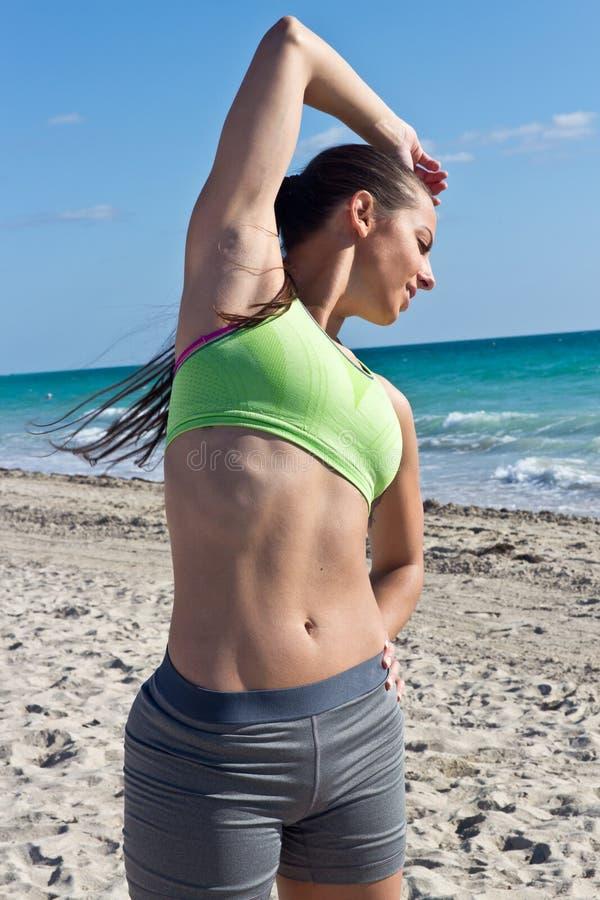 有性感的吸收的妇女在海滩 免版税库存图片